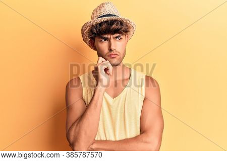 Young hispanic man wearing summer hat thinking concentrated about doubt with finger on chin and looking up wondering
