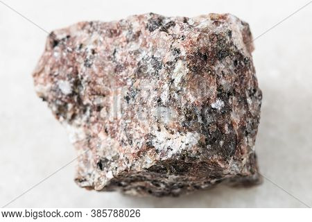 Closeup Of Sample Of Natural Mineral From Geological Collection - Rough Pink Granite Rock On White M
