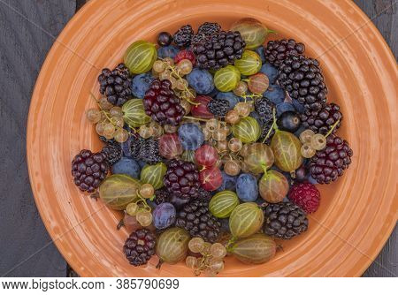 Mixed Color Garden Fruit On Wooden Brown Table And Orange And Green Dish