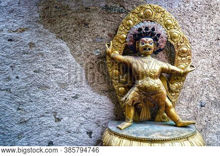 Golden Hindu Statue Of A Crouched Man In Front Of A Wall
