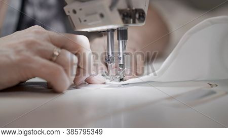 Sewing White Cloth On A White Sewing Machine Close Up. Concept Of Sewing In Modern Bright Studio, Fe