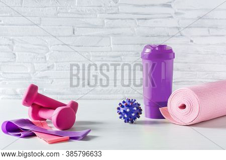 Dumbbells, Fitness Rubber Bands, Yoga Mat And Bottle Of Protein Water On White Floor Over White Bric