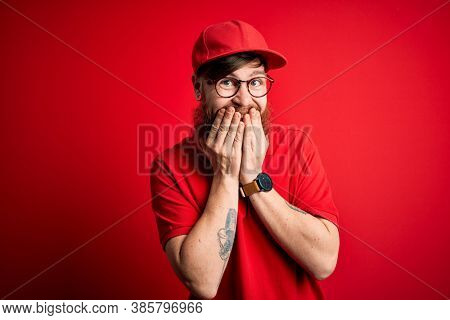 Young handsome delivery man wearing glasses and red cap over isolated background laughing and embarrassed giggle covering mouth with hands, gossip and scandal concept