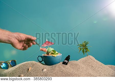 Ice Cream In A Cup, A Drop Of Cbd Oil And A Twig Of Marijuana In The Sand. On The Side Are Sunglasse