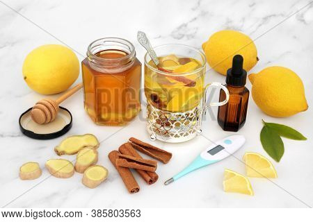 Natural herbal remedy for cold & flu with thermometer and hot medicinal drink with fresh ginger, lemon, honey, cinnamon & eucalyptus essential oil. Traditional immune boosting health care concept.