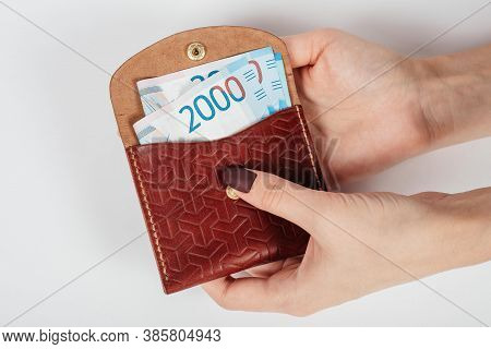 Close-up Of A Womans Hands Putting Banknote Of Thousands Rubles In A Purse.