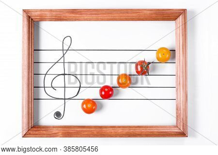Multicolored Cherry Tomatoes On The Musical Staff In The Wooden Frame. Creative Food Background. Sym