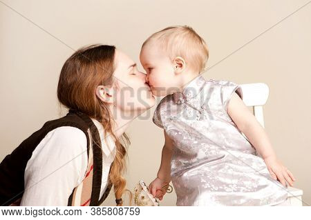 Happy Family. Mum Kisses The Small Daughter. Baby Girl With Short Hair. Children Holiday, Birthday.