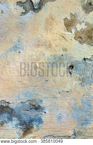 Old Cracked Weathered Painted Wall Background Texture. Light Peeled Plaster Wall With Falling Off Fl