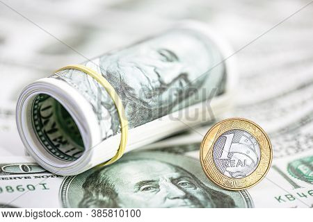 Currency Of A Brazilian Real On Banknotes Of 100 American Dollars. Concept Of High Dollar Against Th