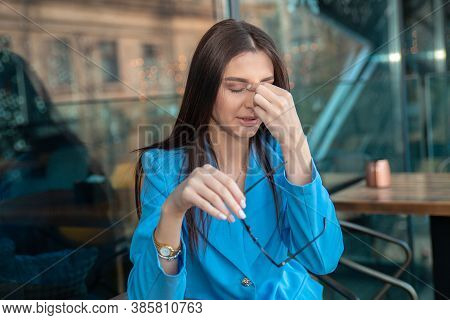 Woman With Glasses Suffering From Eyestrain, Pain In Eyes Or Nose From Specs Sitting At Table At Her