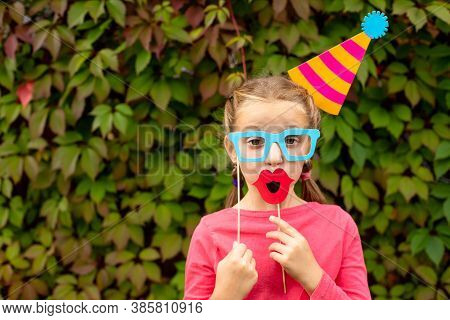 Young Girl Is Preparing For Birthday Party With Photo Booth Props. Photobooth Birthday And Party Set
