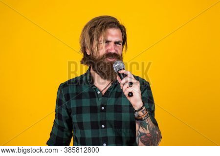 Event Manager. Brutal Man Sing With Microphone. Vocal School. Brutal And Rock. Bearded Man Wear Chec