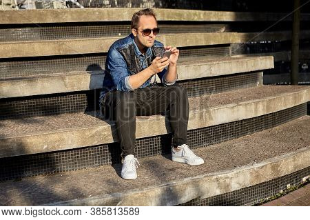 Young Man With Smartphone In Hands Is Sitting On The Beton Stairs And Sending Messages Using His Pho
