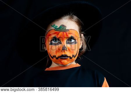 Sad Girl With Pumpkin Makeup On Her Face For Halloween, In A Black Hat, Loneliness And Sadness On Ho