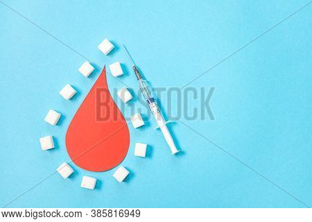 World Diabetes Day. A Large Paper Drop Of Blood And A Syringe On A Blue Background, Around Pieces Of