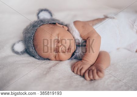 Cute Emotional Newborn Little Baby Boy Sleeping In Crib In A Knitted Suit With Ears. Baby Goods Pack