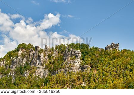 Panorama Of Saxon Switzerland Against A Blue Cloudy Sky In The Elbe Sandstone Mountains From The Riv