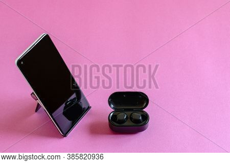 Wireless Earphones, Mobile Phone On The Phone Stand, Pink Background. Modern Technologies Concept.