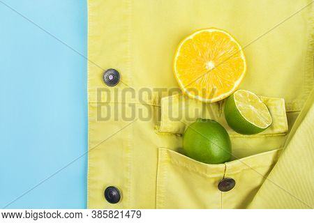 Bright Summer Citrus Flatlay With Lemons And Limes In The Pocket Of Yellow Denim Jacket Isolated On