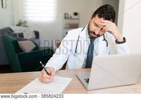 Hispanic Doctor Taking Some Notes From Work And Looking Stressed On A Desk