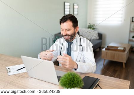 Friendly Hispanic Doctor Working From Home And Talking To A Patient In A Video Call