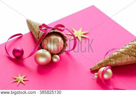 Golden Waffle Ice Cream Cone With Xmas Gold Balls, Stars And Ribbons On Pink Paper. Text Merry Chris
