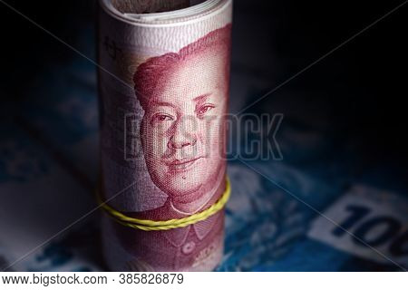 Chinese Currency 100 Yuan Banknote, In A Dark Place, With Banknotes Of 100 Brazilian Reais Defocused
