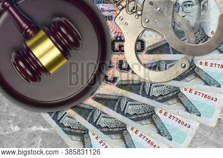 50 Thai Baht Bills And Judge Hammer With Police Handcuffs On Court Desk. Concept Of Judicial Trial O