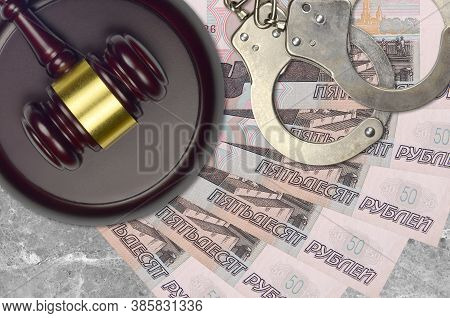 50 Russian Rubles Bills And Judge Hammer With Police Handcuffs On Court Desk. Concept Of Judicial Tr