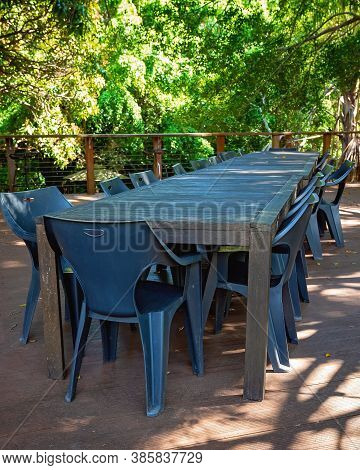 Casual Outdoor Table And Chairs On A Timber Deck Overlooking A Bushland Setting