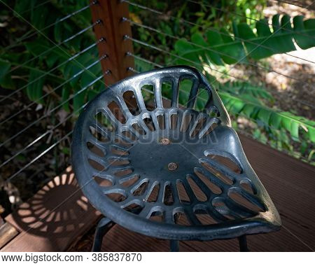 A Decorative Iron Stool Casting Shadows Onto The Timber Deck On Which It Stands