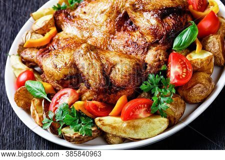 Roast Chicken Served On A White Platter With Roasted Potato, Fresh Tomatoes, Peppers And Herbs On A