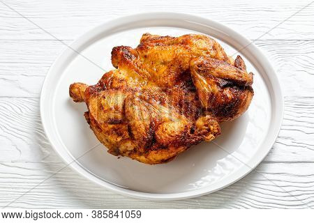 Roast Chicken Served On A White Platter On A Wooden Table, Horizontal View From Above, Close-up