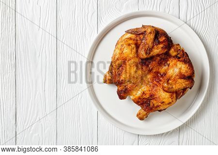 Roast Chicken Served On A White Platter On A Wooden Table, Horizontal View From Above, Close-upflat