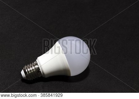 White Light Bulb On The Black Background. It Is A Glass Bulb Inserted Into A Lamp Or A Socket In Cei