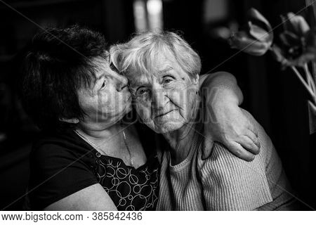An old woman embrace with her adult daughter. Black and white photography.