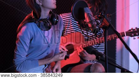 Young Asian Woman Singing While Man In Background Playing Acoustic Guitar. Young Contemporary Sound