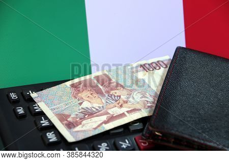 One Thousand Lire Of Italy Banknote With Black Wallet On The Calculator With Italia Flag Background,