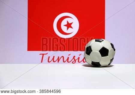 Small Football On The White Floor And Tunisian Nation Flag With The Text Of Tunisia Background. The