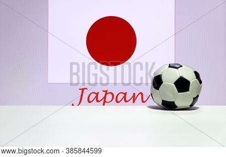 Small Football On The White Floor And Japanese Nation Flag With The Text Of Japan Background. The Co
