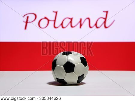Small Football On The White Floor And Polish Nation Flag With The Text Of Poland Background. The Con