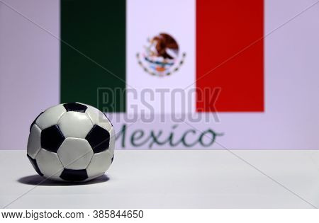 Small Football On The White Floor And Mexican Nation Flag With The Text Of Mexico Background. The Co