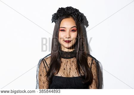 Image Of Smiling Devious Young Witch Looking At Camera With Cunning Smirk, Standing Over White Backg