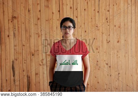 Woman Wearing Iraq Flag Color Shirt And Standing With Two Hands In Pant Pockets On The Wooden Wall B