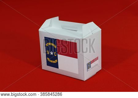 North Carolina Flag On White Box With Barcode And The Color Of State Flag On Red Background. The Con