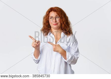 Skeptical And Unamused, Smirking Redhead Middle-aged Woman Looking And Pointing At Something Average
