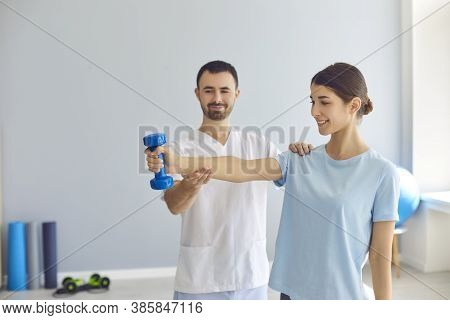 Doctor Teaching Young Woman To Do Osteoporosis Treatment Exercise With Dumbbells