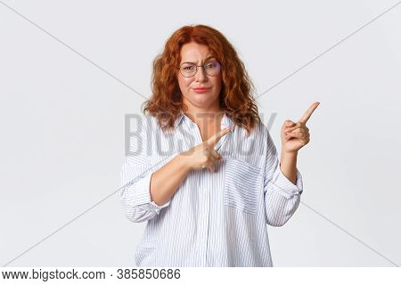 Skeptical And Unamused Redhead Middle-aged Woman Smirk Displeased, Having Doubts, Pointing Fingers U