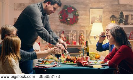 Head Of The Family Cutting The Chicken At Christmas Reunion. Traditional Food. Winter Holidays Celeb